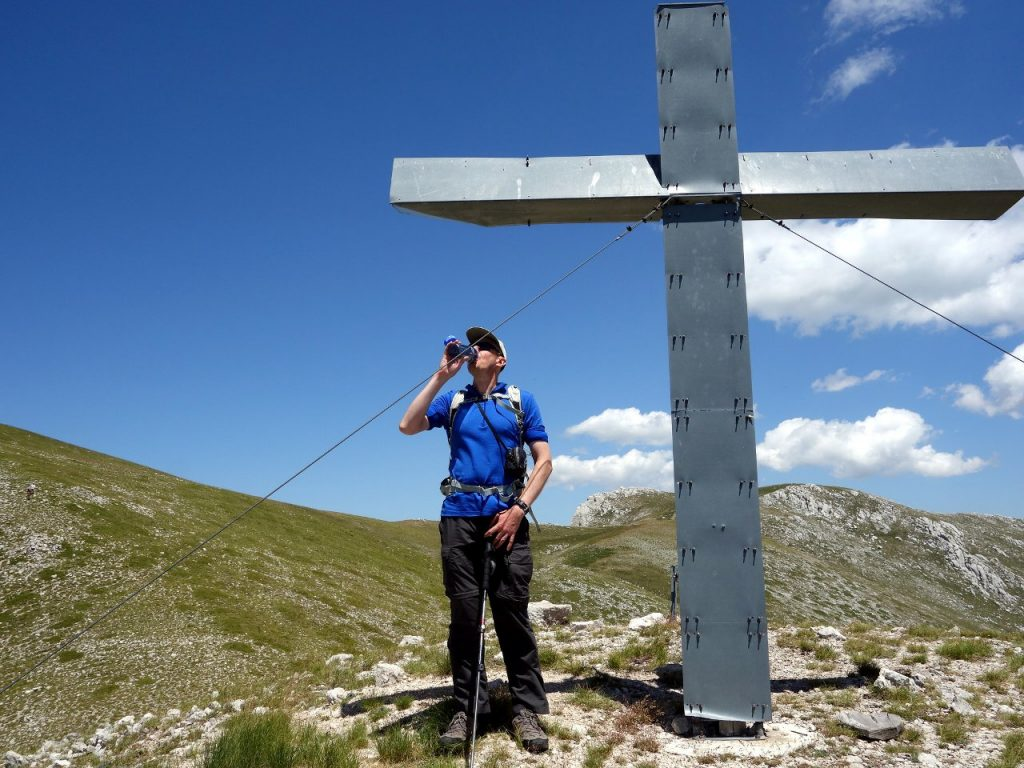 Taking a swig beside Monte Calanga's ludicrously oversized summit monument