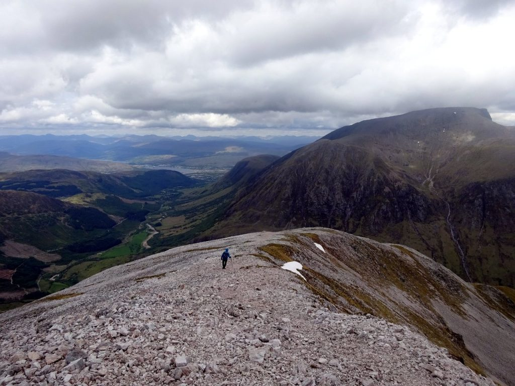 Descending the apron of shattered granite on top of Sgurr a Mhaim, with Ben Nevis across the valley of Glen Nevis