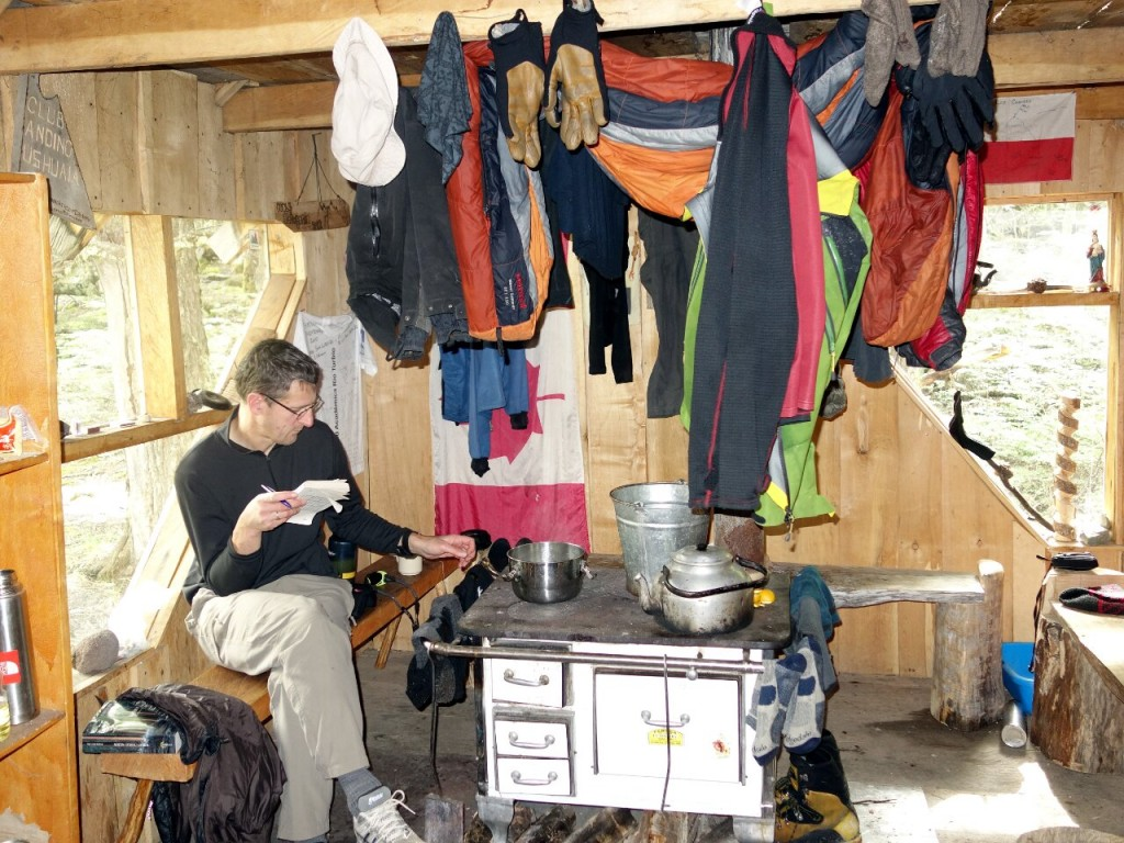 Dave dries out his wet things over the stove at Toni Rohrer Refugio
