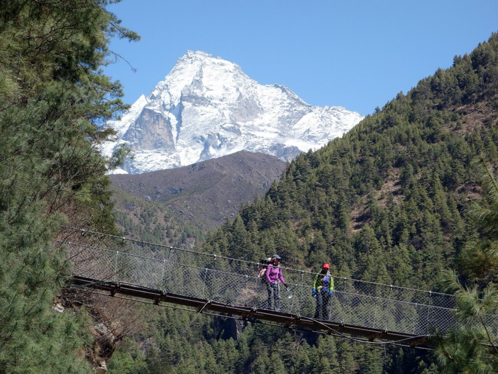 Crossing a bridge in the wooded Dudh Kosi gorge on the trail from Phakding to Namche Bazaar, with Khumbila behind