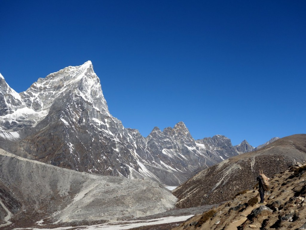 A porter looks across at the east face of Cholatse from near Dingboche on the Everest Base Camp trail