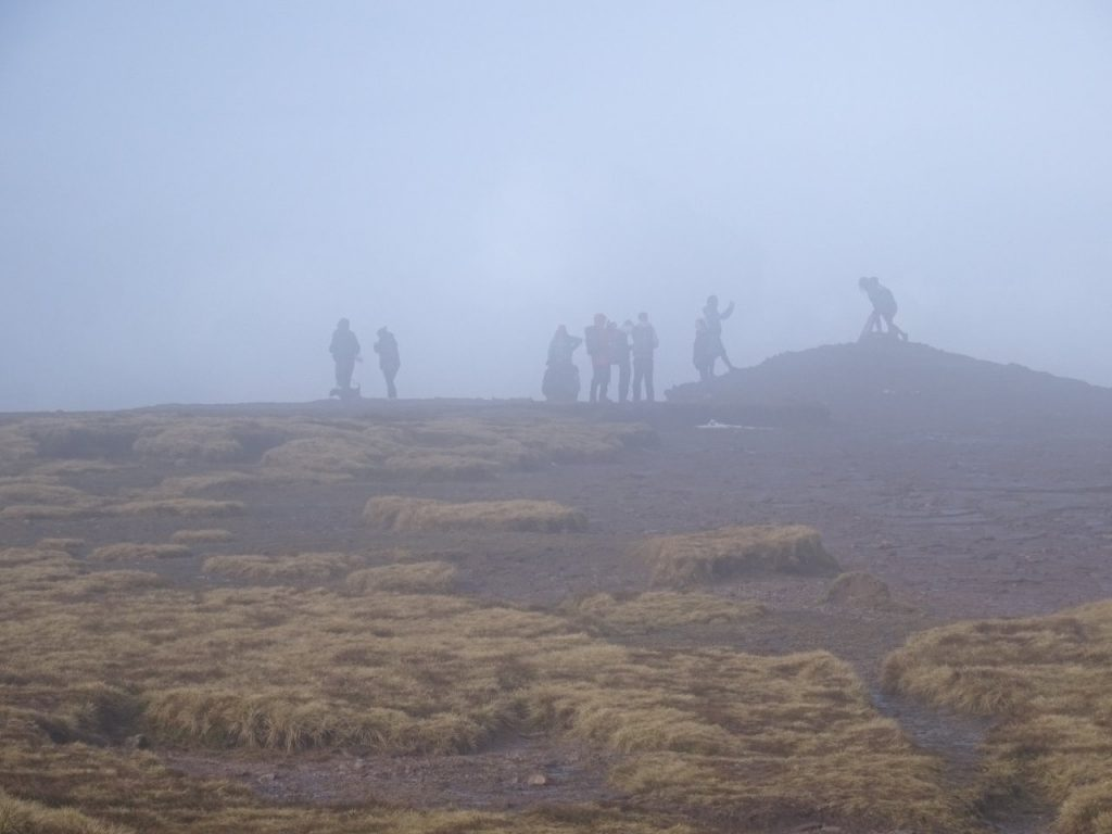 Figures seen through mist on Pen y Fan's summit plateau