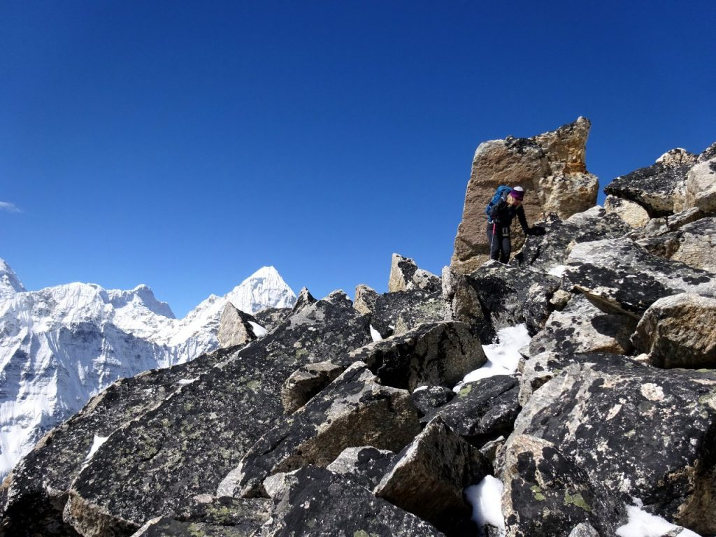 Scrambling along Drohmo Ri's summit ridge, with Ramtang Peak (6,700m) and Wedge Peak (6,802m) on the horizon