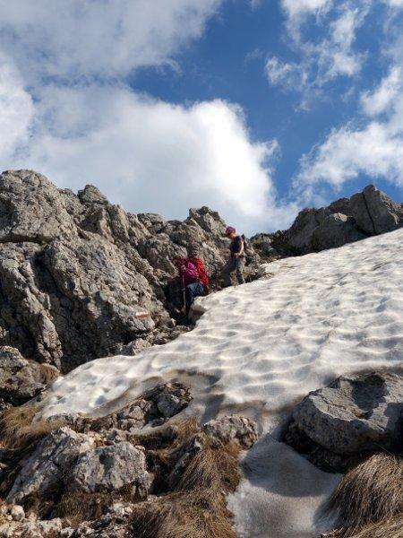 Skirting around a snow patch beneath the summit ridge
