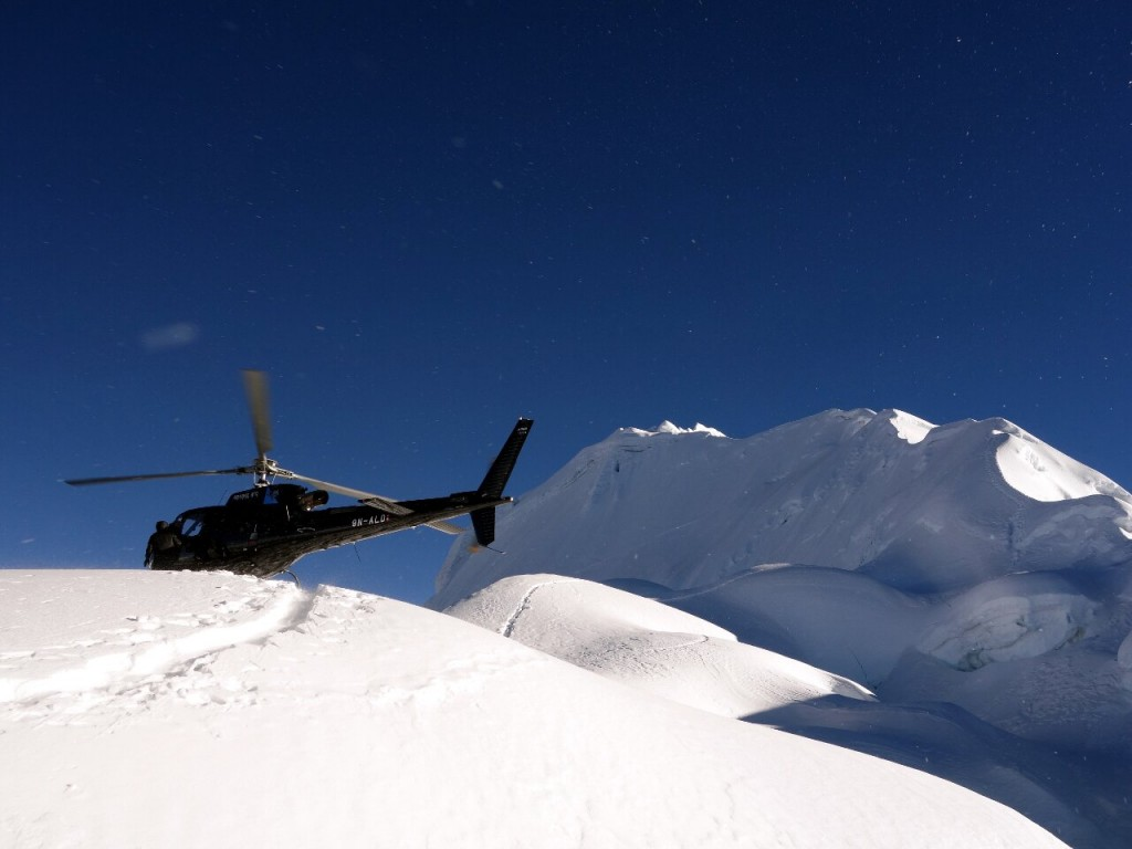 A helicopter lands close to the summit of Cholatse to perform a rescue