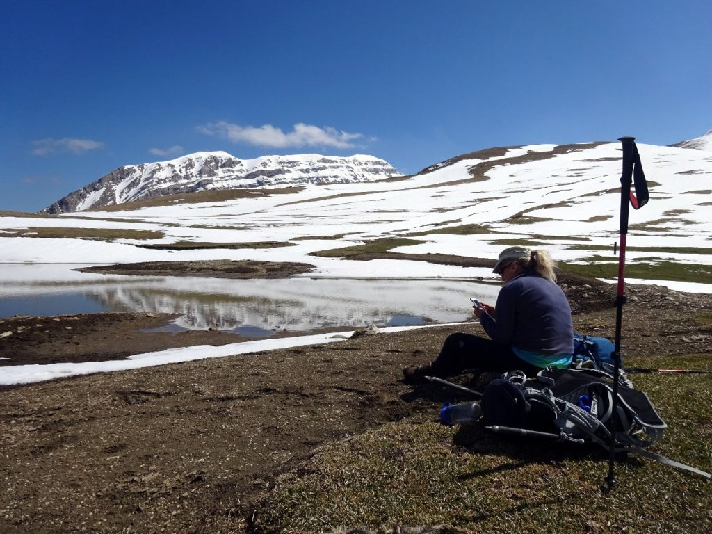 Edita has a snack beside a pool on Piano di Camarda, as the ridge of Monte Corvo rises the other side of the valley