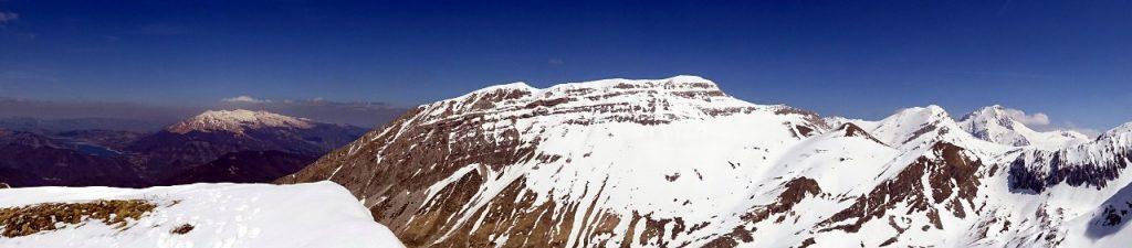 The dramatic view north from the summit of Pizzo di Camarda: Lago di Campotosto, the peaks of Monti della Laga (distance), the long ridge of Monte Corvo (2,623m) seen across the Chiarino Valley, and the white pyramids of Pizzo d'Intermesoli (2,635m) and Corno Grande (2,912m) seen behind the ridge