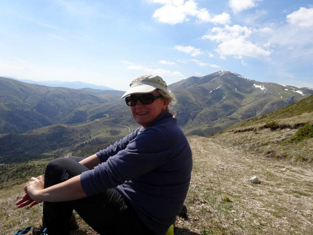 A relaxed Edita takes a rest in the sun on the way down, with Monte San Franco behind