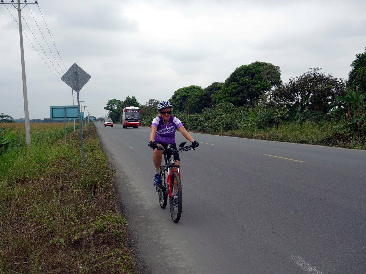Edita cycles across the flat plains of rice fields between Babahoyo and Montalvo