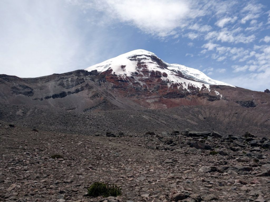 The west face of Chimborazo from Carrel Hut car park. The west ridge (El Castillo) route forms the left-hand skyline, while the Whymper route goes up the right-hand skyline from the pinnacles on the far right. The normal route angles up diagonally to the glacier on the left-hand skyline roughly following the line between the grey and the red rock on the face. To traverse from the Whymper route onto the normal route it's necessary to find a route across the red rock of the west face.