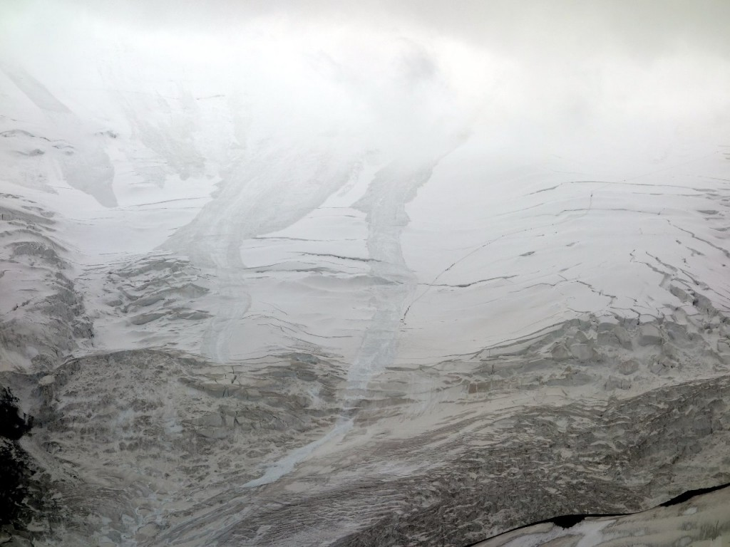 Crevasses and avalanche trails on the north face of Peak Lenin, with figures on the route to Camp 2 curving off to the right