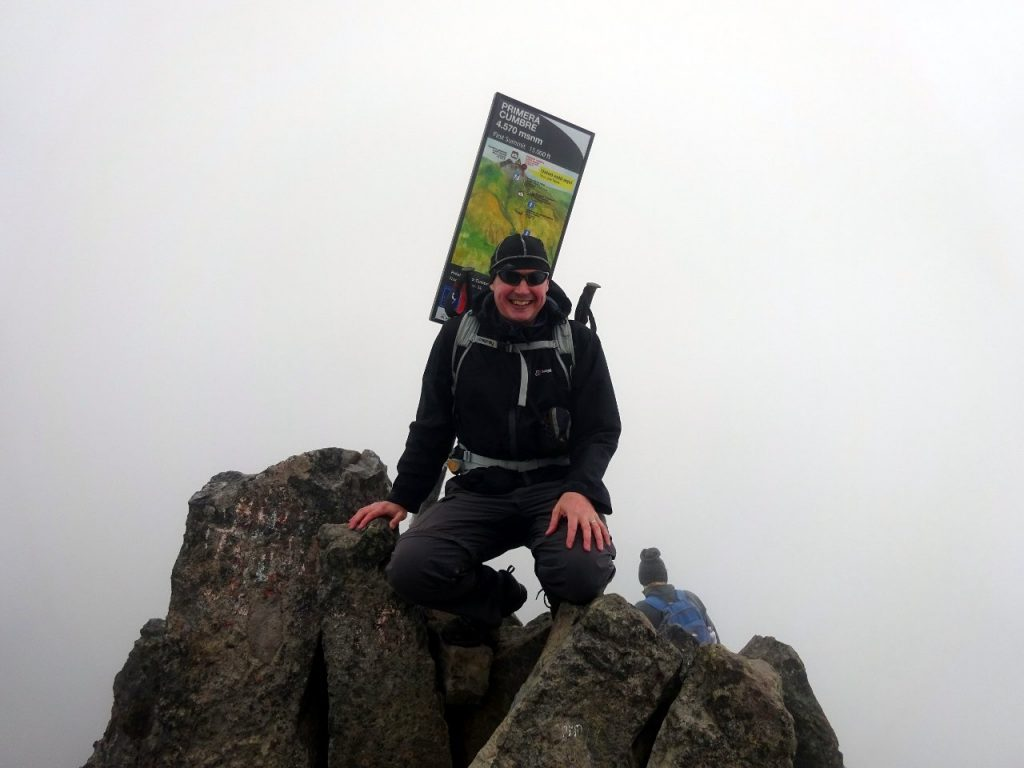 Me on the first summit (4,570m) with the helpful information board behind me