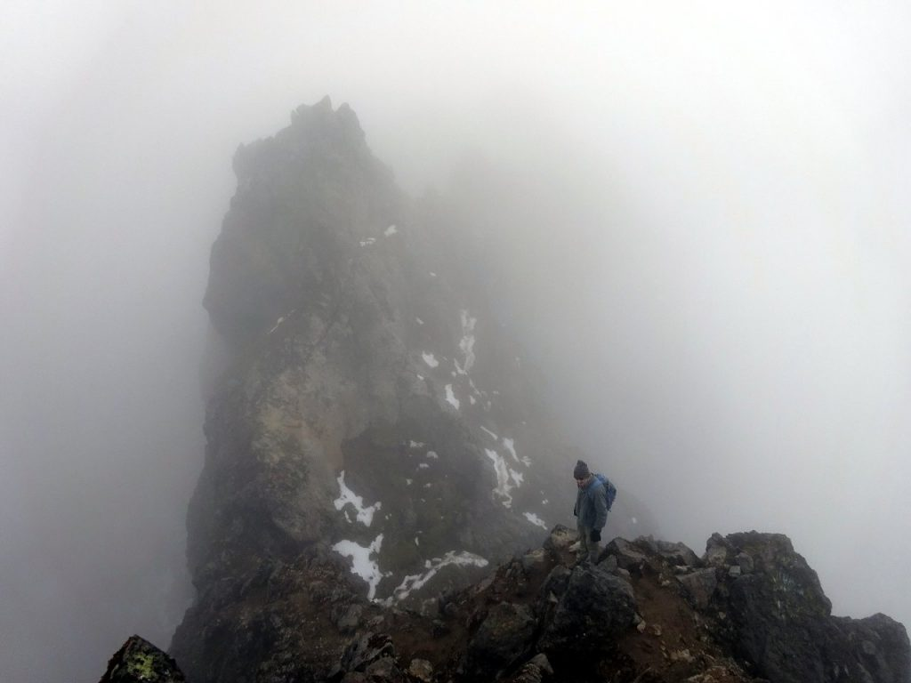 A rock tower looms out of the mist