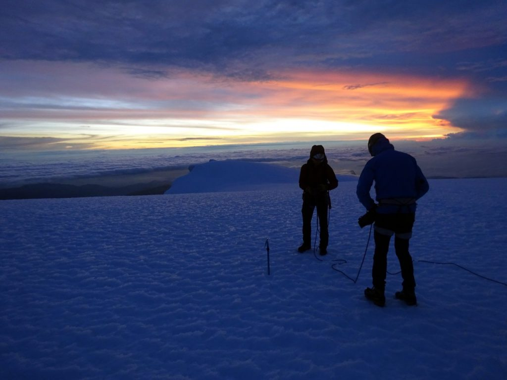 On the summit with an orange glow on the horizon and the second summit behind