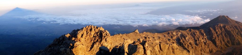 Mount Meru's summit ridge, with the shadow of the summit cast over the landscape to the left