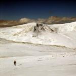 Walker on Beinn Mhanach's summit plateau, with Beinn Achaladair on the horizon