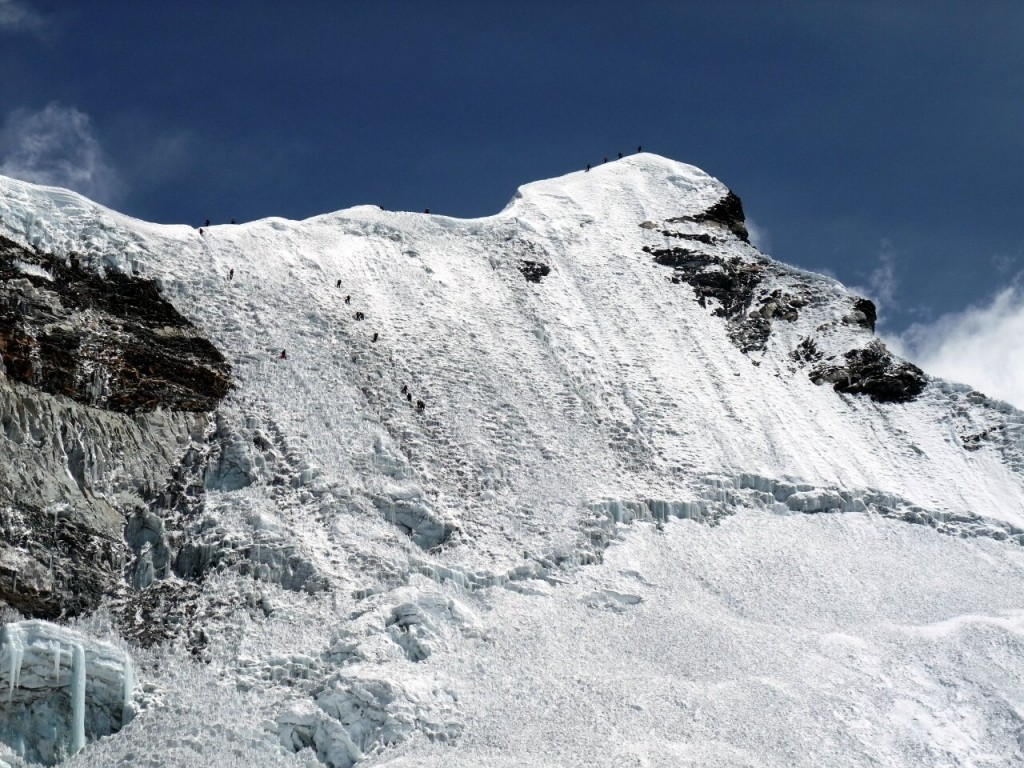 The headwall and summit ridge of Island Peak crawling with climbers