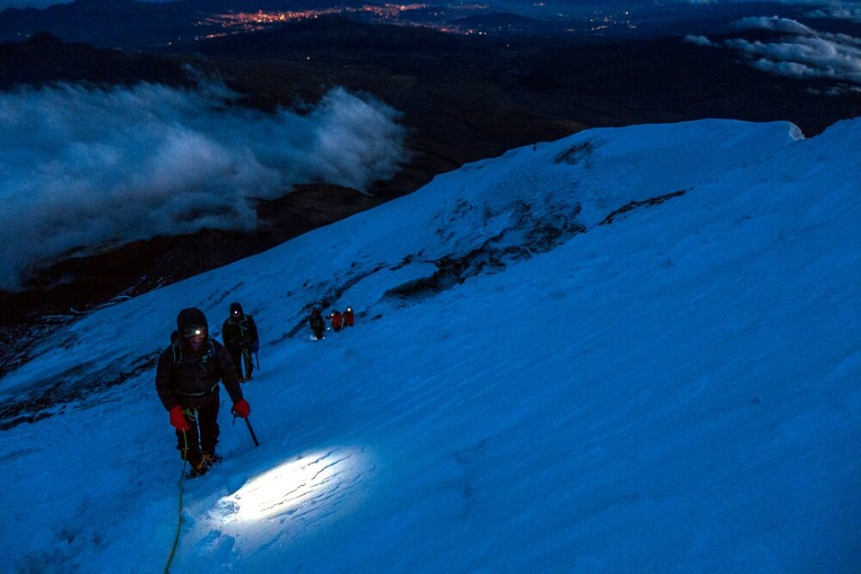 Climbing Cotopaxi by torchlight, with the lights of Quito far below (Photo: Estalin Suarez)