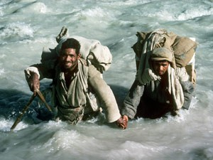 Balti porters crossing a river during the difficult trek in to the base of The Ogre (Photo: Doug Scott)
