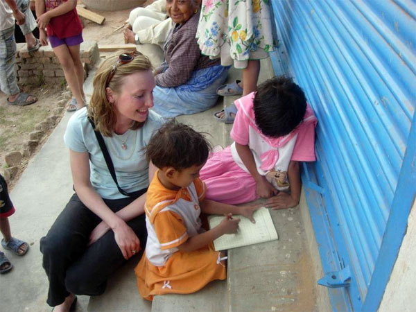 CHANCE founder Tina Stacey helps kids do homework at a village in the Kathmandu Valley (Photo: CHANCE)